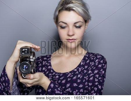 Film student posing with a classic video camera advertising for Hollywood movie industry or art schools. She can depict a director cinematographer filmmaker or a camerawoman.