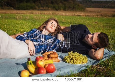 Girl and guy having picnic on the field. couple lying on the green lawn