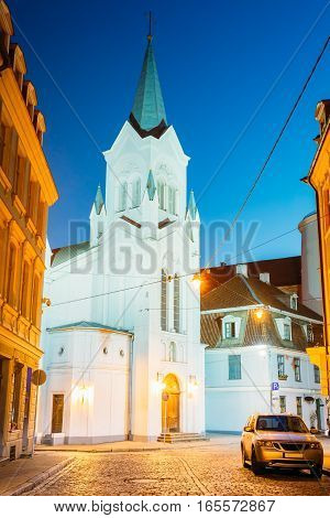 Riga Latvia. The White Tower With Pyramidal Spire Of Our Lady Of Sorrows Or Virgin Of Anguish Church, Ancient Catholic Church On Pils Street In Evening Illumination Under Summer Blue Sky