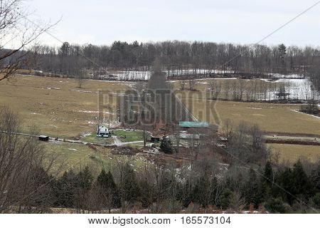 A house and barn with a horse and lawn decorations.