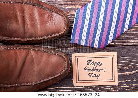 Greeting card, shoes and tie. Necktie on wooden surface. Footwear defines the whole look.