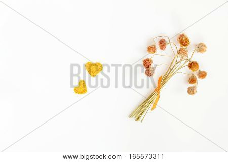 Dry little flowers with orange ribbon and two orange crochet heart. Flat lay on white background top view.