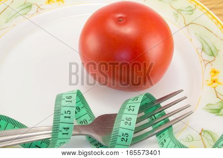 Measuring tape and a fork with tomato isolated on background concept of healthy food and diet