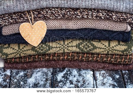 Stack of winter sweaters knitted on a wooden background