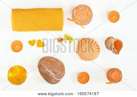 Spa attributes sets. Honey bath salts dry flowers soap cosmetic cream cosmetic oil candles shell stone and towel. Yellow orange concept. Flat lay on white background top view.