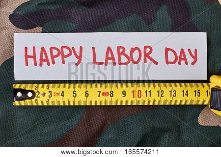 Labour Day card on camouflage. Greeting paper and tape measure. Preparing for holiday.