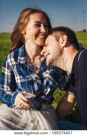 man and woman laughing on a picnic. she drinking wine