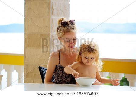 Kid eats himself sitting with mother at table on outdoor terrace with columns on natural background.