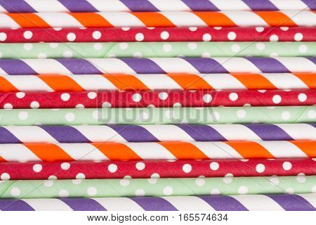 Colorful drinking striped straws as a background.