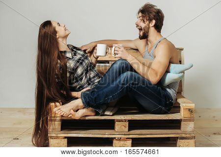 Young happy couple of pretty girl or cute woman with brunette long hair and handsome man or muscular macho with muscular torso sits on wooden with tea cups pallet sofa on grey background