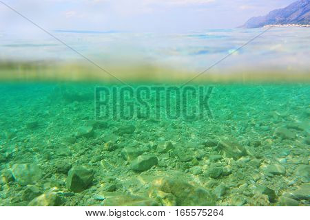 Shallow sea with stones pebbles on seabed partly underwater and partly above water.