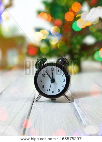 Vintage clock shows twelve without five minutes blurred background with a Christmas tree and bokeh