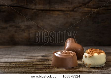 Three different types of chocolate candy over rustic wooden background