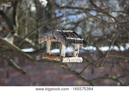 nice and small handcrafted wooden bird feeder from birch branches with wicker roof hanging on a tree