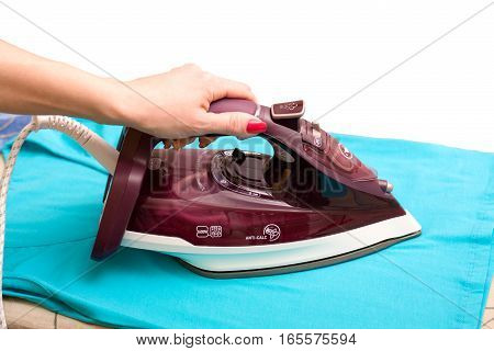 Steam iron in a female hand isolated on white background. blue T-shirt ironing