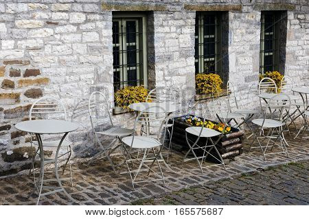 Tables and chairs outside a traditional house in the stone village of Papigo in Epirus, Greece