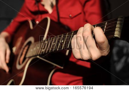 Guitarist in red shirt. Close-up of a human hand on the strings of red acoustic guitar. Shallow depth of field.