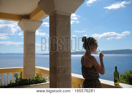 Pretty woman drinking white wine from glass on balcony with columns on seascape background.