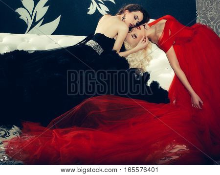 two pretty women in elegant evening dresses with long veil skirts red and black colors in jewellery earrings with gem stones in room