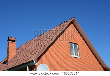 Red Metal Roofing New Attic Brick House. Old faded red metal roof tile and chimney. Roofing Construction.