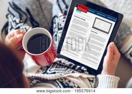 Woman in home cozy clothes sitting on a sofa using a tablet and a red cup of coffee in her hands. Online education concept. e-learning. top view