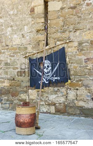 Pirate attributes flag and a powder keg at the old wall