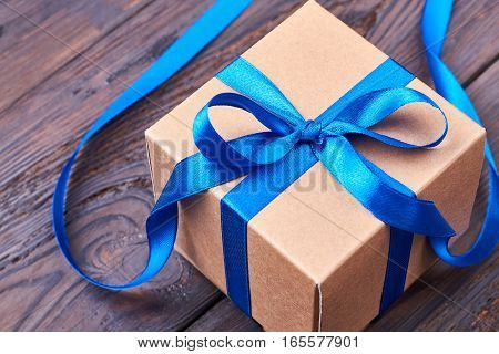 Gift box with blue ribbon. Present box on wood. Traditional item for festive mood.