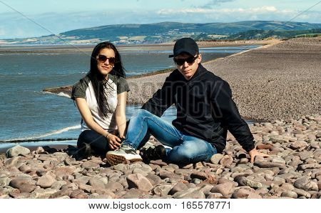 Happy young couple in love relaxing in a beach of Minehead UK enjoying ocean view together.