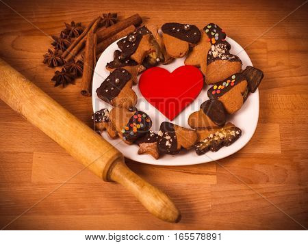 Heart cookies on a wooden brown background, rolling pin. Concept of Holiday Valentine's Day or Christmas and New Year. Top view of assorted cookies covered with chocolate, gift for Valentines Day.