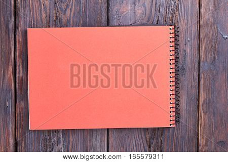 Notebook with spiral on wood. Peach color notepad on table. Equipment for studying.