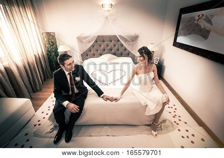 Newlyweds in bedroom with heart. Newlyweds in bedroom with heart. First night. On the bed rose petals heart-shaped.