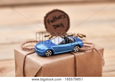 Toy car on gift box. Father's Day card and bow. Speed of life.