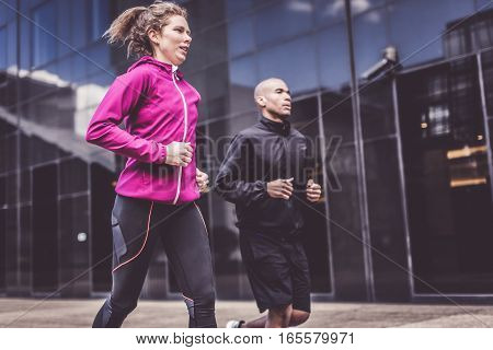 Multi-ethnic couple jogging in urban setting, La Defense, Paris, France.