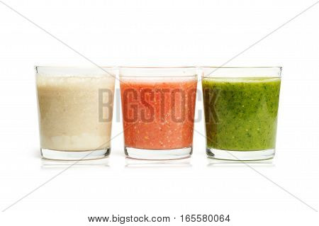 Three glasses with herbs, strawberry and banana smoothies isolated on white background