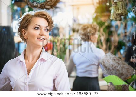 Dreamful woman is enjoying work in flower shop. She is looking aside and smiling