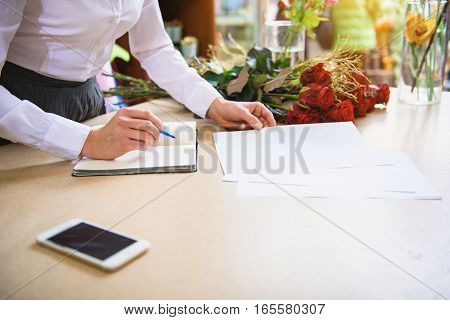 Close up of female hands writing order of client about flower sale down. Woman is standing at table and holding papers