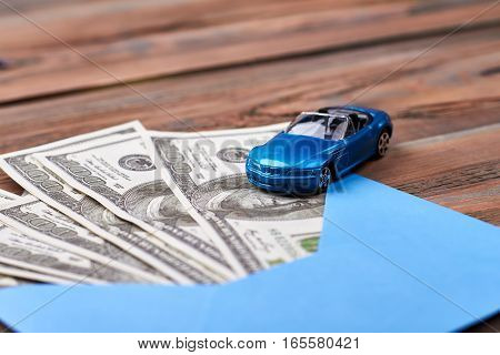 Money in envelope near car. Plastic toy car near dollars. Build your business.