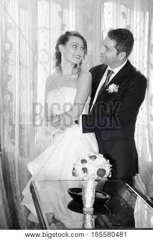 Happy bride and groom newlyweds in the house. Black and white. Inside the house with flowers on the table. Behind them a window with a decorated curtain.