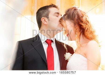 Romantic kiss of newlyweds. Husband kiss his wife on the forehead. Romantic scene of marriage, in the house in front of a colorful tent. Intense light.