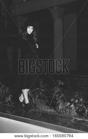 Black and white art photography monochrome, girl in hat standing against the city