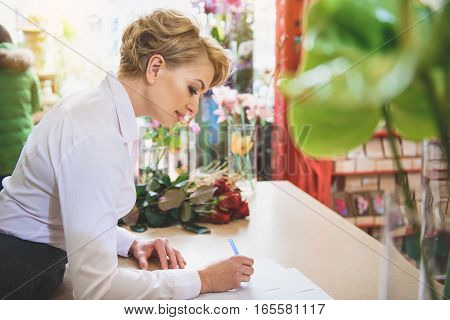 Joyful female florist is writing on papers with concentration. She is standing at table and smiling