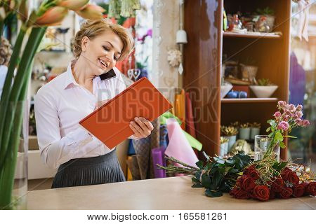 Happy female florist is receiving an order with joy. She is talking on mobile phone and making notes. Woman is standing and laughing