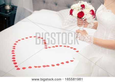 Marry, marriage. Bride at home. Bridal bed. Petals heart shape. Figure of a woman with a bouquet of flowers in her hand in front of the bridal bed in the bedroom. Rose petals in a heart shape on the bridal chamber. Wedding dress