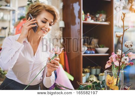 Serene woman is admiring the flower and smiling. She is using phone for communication while working in store