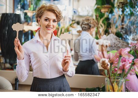 Joyful female florist is holding wooded figures and smiling