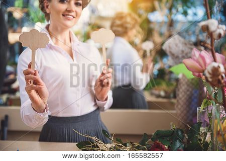 Cheerful woman is showing wood objects to camera in flower shop. She is standing and smiling with confidence