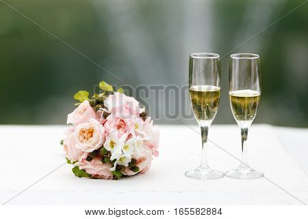 Two glasses of champagne on the background of the wedding bouquet of pink roses. Soft focus selective focus