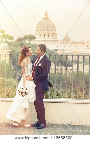Outdoor wedding couple in town. A pair of newlyweds embracing each other in the historic center of Rome, Italy. Behind them, in the background, the dome of St. Peter in the Vatican.