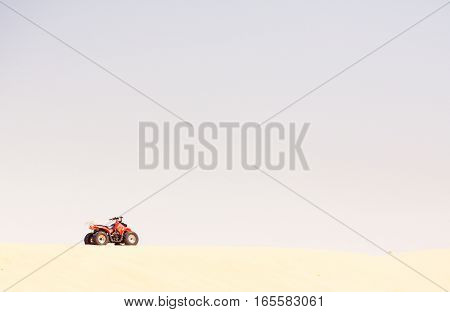 a red quad bike parked at the top of a sand dune