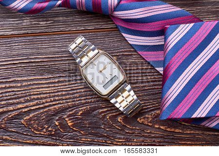 Watch near striped tie. Necktie on wooden surface. Punctuality is important for business.